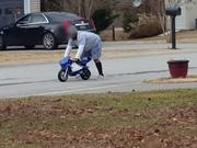 Large Man Driving A Mini Bike