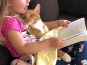 Little Girl Telling Her Cat A Bedtime Story